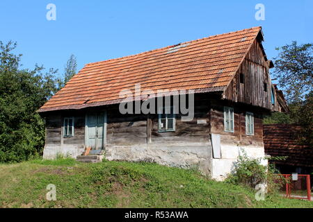 Small wooden old family house with dilapidated boards and broken roof with missing roof tiles on top of small hill surrounded with grass and trees - Stock Photo