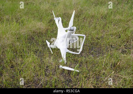 The crashed drone. Dirty and in the juice of the grass is a quadrocopter. - Stock Photo
