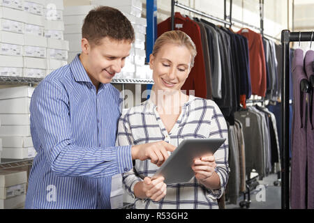 Couple Running On Line Fashion Business In Warehouse - Stock Photo