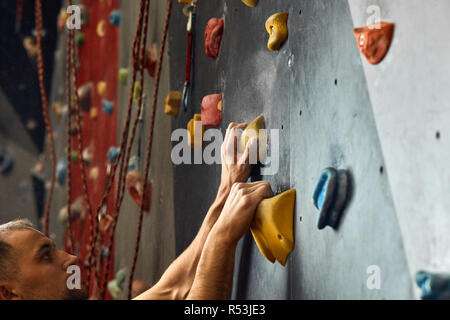 Macro shot of climbers hands gripping colourful handholds during indoor workout - Stock Photo