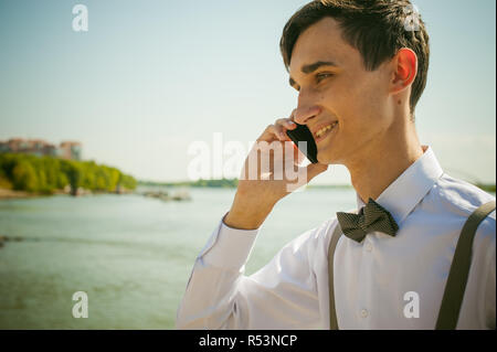 young skinny man, elegantly stylishly dressed in white shirt, gray trousers with suspenders and bow tie. Portrait of young guy talking on phone on background of river on warm sunny summer day - Stock Photo