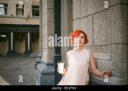 drinks coffee from a cup. woman with dyed red hair in a pale pink dress with a backpack white color drinking coffee, holding a paper cup of Take away, on a city street a warm summer day, behind, a huge exclusive doors - Stock Photo