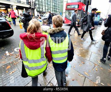 Primary school children wearing hi vis jackets on a school trip in London, England, UK. - Stock Photo