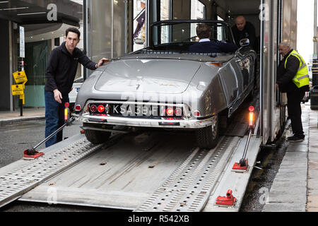 London, UK. 29th November, 2018. Bonhams' staff move a 1966 Citroen DS-21 Decapotable, a very rare right-hand drive example and believed to be only one of six extant, in preparation for an auction of historic and high-performance racing and road cars. Highlights include a Le Mans class-winning Jaguar XJ220C driven by David Coulthard (£2,200,000-2,800,000), a Lister Jaguar Knobbly (£2,200,000-2,800,000) and a 1958 BMW 507 owned by its designer, as well as Ferraris, Aston Martins, Bentleys, Porsches and Jaguars. Credit: Mark Kerrison/Alamy Live News - Stock Photo