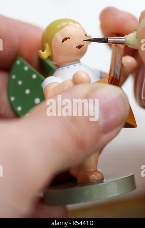 08 November 2018, Saxony, Grünhainichen: An employee of the Wendt&Kühn manufactory paints the face of an angel figure. Carving and the production of wooden toys are still an important branch of the economy in the Erzgebirge. The spectrum ranges from the classic two-man family business to large medium-sized companies. With almost 200 employees, Wendt&Kühn is one of the larger companies in the industry. Photo: Jan Woitas/dpa-Zentralbild/dpa - Stock Photo