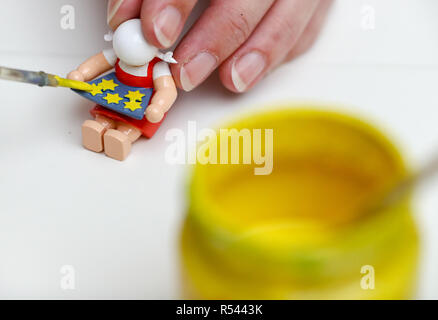 08 November 2018, Saxony, Grünhainichen: An employee of the manufactory Wendt&Kühn paints the figure 'Sterntalermädchen'. Carving and the production of wooden toys are still an important branch of the economy in the Erzgebirge. The spectrum ranges from the classic two-man family business to large medium-sized companies. With almost 200 employees, Wendt&Kühn is one of the larger companies in the industry. Photo: Jan Woitas/dpa-Zentralbild/dpa - Stock Photo
