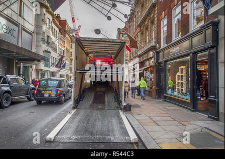 Bonhams, New Bond Street, London, UK. 29 November 2018. Historic cars arrive at Bonhams in central London for the car sale taking place on 1st December 2018. Image: Cars are unloaded in New Bond Street under the Christmas decorations and alongside designer shops in morning rush-hour traffic. Credit: Malcolm Park/Alamy Live News. - Stock Photo