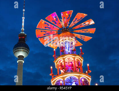 Berlin, Germany. 29th Nov, 2018. The traditional colourful Pyramiden Treff or Pyramid meeting place contrasts with the Television Tower or Fernsehturm at the Christmas Market held at Alexanderplatz in Berlin, Germany. Credit: Iain Masterton/Alamy Live News - Stock Photo