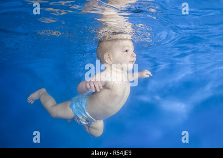 Little baby boy learns to swims underwater. Baby swimming underwater in the pool on a blue water background. Healthy family lifestyle and children wat - Stock Photo