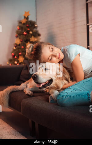 beautiful smiling young blonde woman on couch hugging golden retriever dog at christmas time - Stock Photo