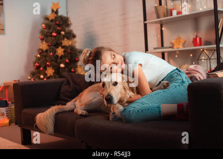 beautiful content young blonde woman on couch hugging golden retriever dog at christmas time - Stock Photo