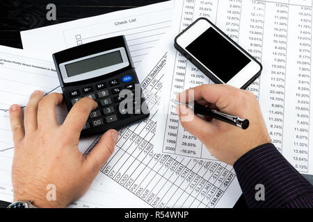 Young businessman using elegant pen, calculator and smartphone at the office. Financial reports, business papers on the desk. - Stock Photo