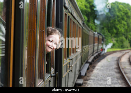 Passenger young girl aged 6 / six years old, smiling & looking out of the window of a moving train carriage on the Isle of Wight steam Railway line. UK (98) - Stock Photo