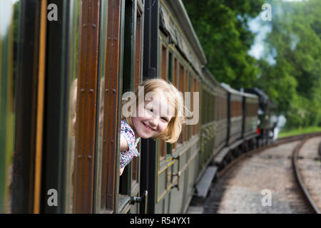 Passenger young girl aged 8 / eight years old, smiling & looking out of the window of a moving train carriage on the Isle of Wight steam Railway line. UK. (98) - Stock Photo