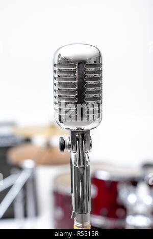 Microphone in a recording studio with drum on background. - Stock Photo