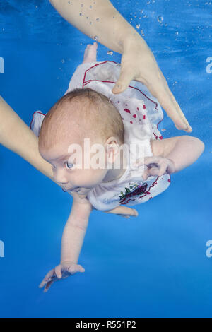 1.5 months girl in a white dress swims underwater in the pool, mother holding the child. Healthy family lifestyle and children water sports activity.  - Stock Photo