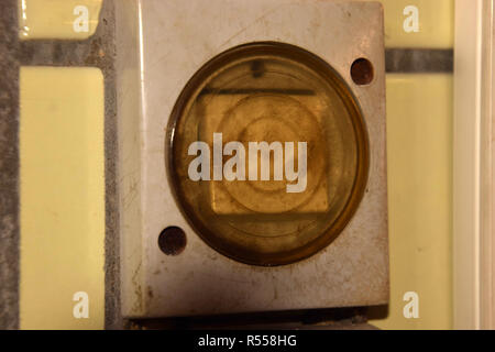 outdated dirty light switch on a tiled wall in a stable, old and dirty light switches with plastic cover protected against moisture and wet - Stock Photo