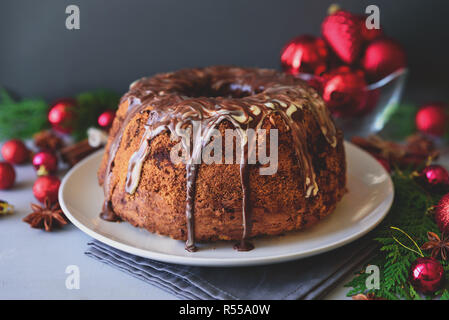 Christmas cake with chocolate icing on gray wooden background. Holiday decorations concept. Toned - Stock Photo
