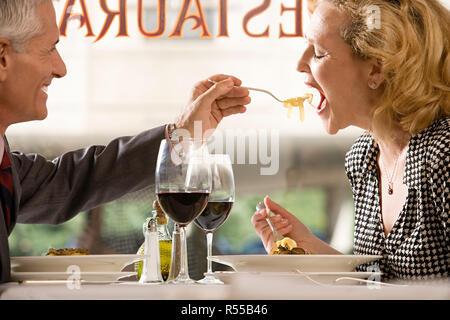 Man feeding pasta to woman - Stock Photo