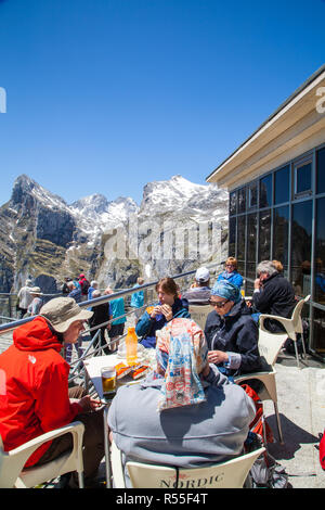 People sitting eating and drinking at the cafe at the top of Fuente De after taking the cable car up the mountain in the Picos de Europa Spain - Stock Photo