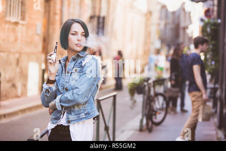 Portrait of a young woman smoking an electronic cigarette in the street - Stock Photo