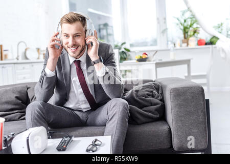 smiling handsome businessman in headphones sitting on couch at home - Stock Photo