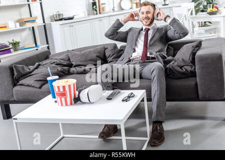 smiling businessman in headphones sitting and relaxing on couch at home - Stock Photo