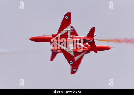 Royal Air Force RAF Red Arrows display team Hawk jet planes opposition pass at the Royal International Air Tattoo, RIAT, RAF Fairford airshow. Close - Stock Photo