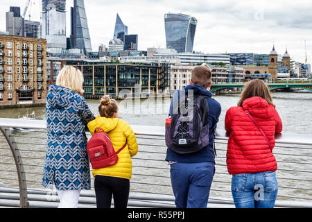 London England United Kingdom Great Britain Millennium Bridge steel suspension crossing Thames River water city skyline metal railing man woman girl l - Stock Photo