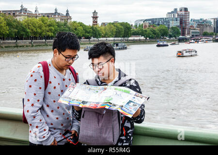 United Kingdom Great Britain England London Westminster Bridge Thames River Asian man boy teen reading map city skyline - Stock Photo