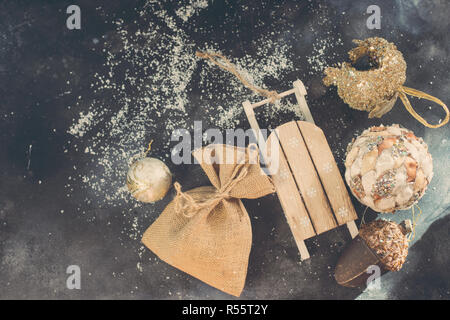 christmas golden toys and gift bag on a wooden sleigh, retro style background - Stock Photo