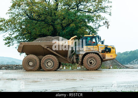 A Volvo A40F dumpster carries a load of rubble in a quarry - Stock Photo