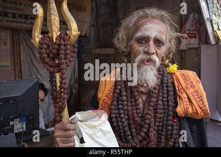 A sadhu or Hindu holy man with a ritual trishul (trident) and a necklace from Rudraksha seeds, soliciting alms in Kalbadevi area, Mumbai, India - Stock Photo