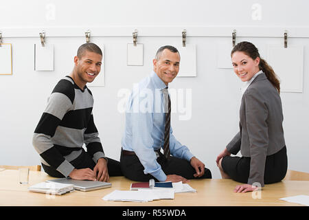 Colleagues sitting on table - Stock Photo