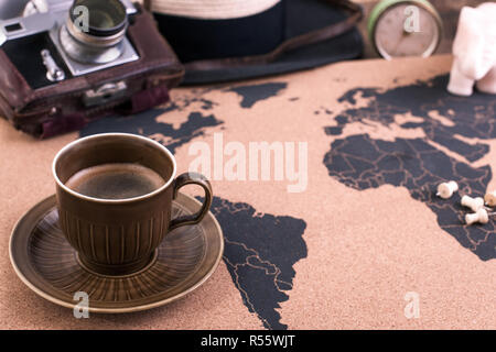 A cup of fragrant coffee on the map, an old camera and a route plan, a vintage photo. Travel and holidays. Copy space - Stock Photo