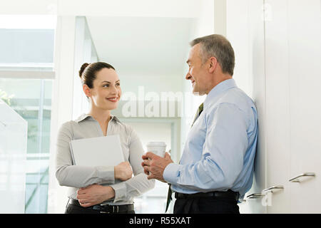 Two business colleagues talking in corridor - Stock Photo