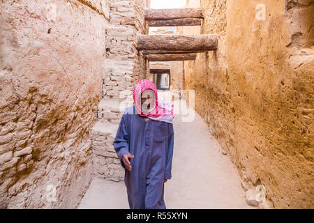 Dakhla Oasis, Egypt. Old Arabian Egyptian man walking dressed in blue national male dress thawb, by medieval street through ancient town in Al Qasr. - Stock Photo