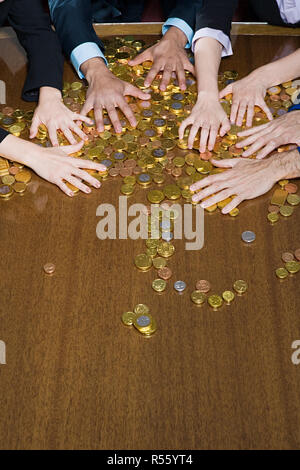 Hands grabbing coins - Stock Photo