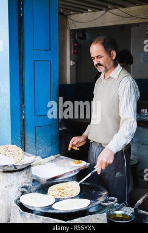 KATHMANDU, NEPAL - APRIL 2015: street cook baking roti bread in his open street shop. Vertical orientation. - Stock Photo