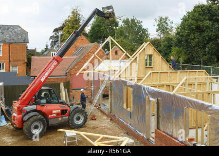 Buckingham, UK - October 13, 2016. Heavy machinery lifts a roof truss into place on an extension to a period house. The extension is of timber frame c - Stock Photo