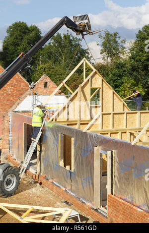 Buckingham, UK - October 13, 2016. A builder at work on a building site in the UK installs roof trusses to a timber frame house extension - Stock Photo