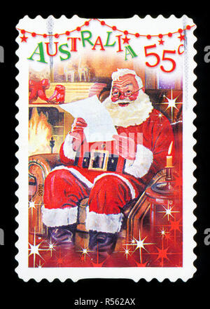 AUSTRALIA - CIRCA 2010: A used postage stamp from Australia, depicting a festive scene of Santa Claus reading a letter by the fireplace, circa 2010. - Stock Photo