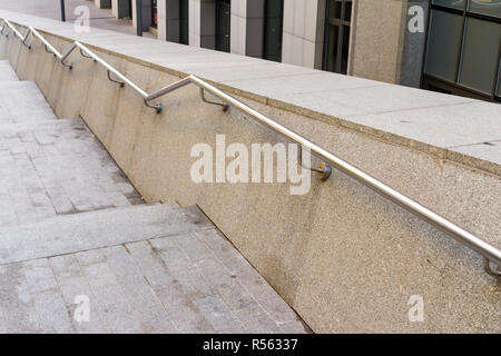 stainless steel metal handrails on stone steps - Stock Photo