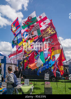 Enfield, London, uk - May 24, 2014:  Multitude of flags flying at a car show. - Stock Photo