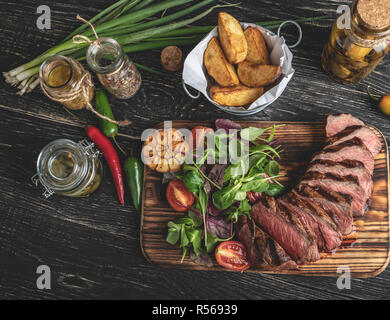 sliced juicy steak medium rare on the board with herbs, fried potatoes, spices on a black surface - Stock Photo