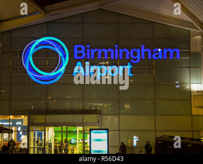Illuminated sign on the front of the terminal building of Birmingham airport at night - Stock Photo