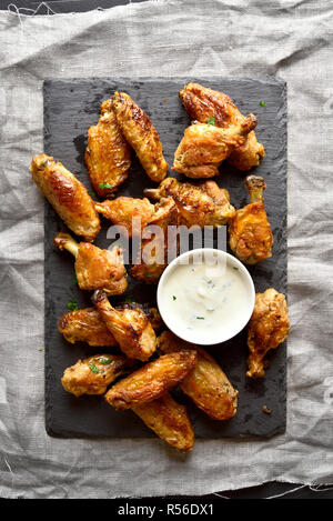 Roasted chicken wings with sauce on slate board. Top view, flat lay - Stock Photo