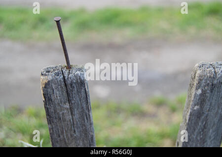 Old wooden fence and a rusty nail sticking out - Stock Photo