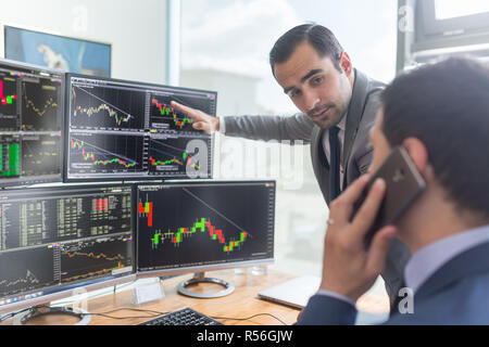 Stock brokers looking at computer screens, trading online. - Stock Photo