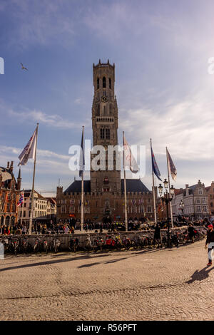 Bruges, Belgium - 17 February 2018: Belfry of Bruges, a group of people walking in front of a clock tower with Belfry of Bruges in the background - Stock Photo